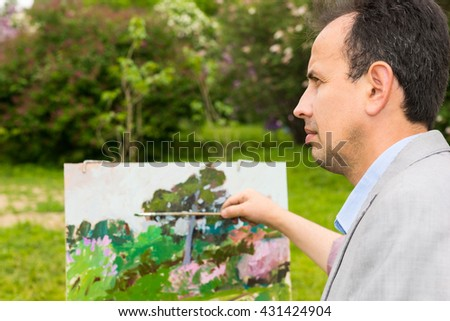 Portrait of a pensive professional artist painting in a garden and holding a paintbrush standing in front of his easel - stock photo