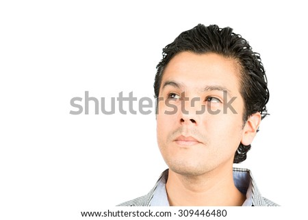 Portrait of a pensive, reserved, handsome hispanic man looking up to the side at blank copy space or product with serious facial expression showing deep thought, curiosity, interest, wonder - stock photo