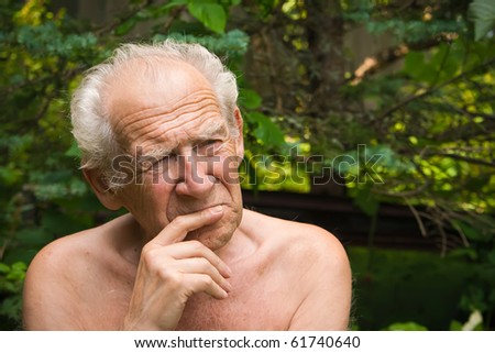 portrait of a pensive senior man holding his hand near his face - stock photo
