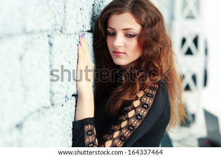 Portrait of a pensive woman leaning at the brick wall