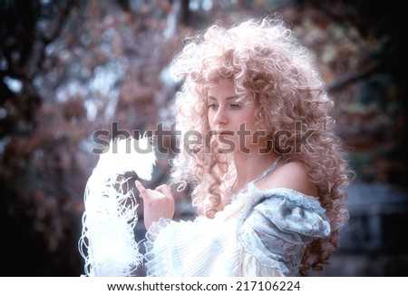 Portrait of a pensive woman looking at the white feather in her hands - stock photo