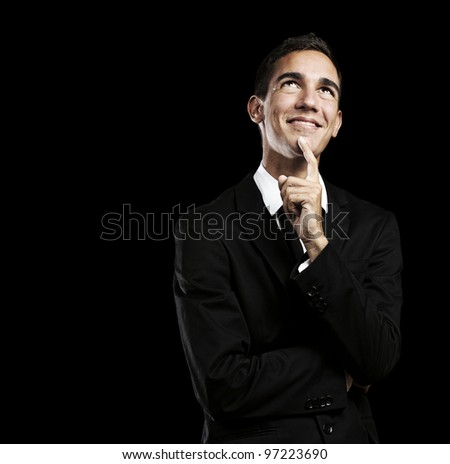 portrait of a pensive young business man against a black background - stock photo