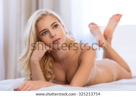 Portrait of a pensive young girl in lingerie lying on the bed at home - stock photo