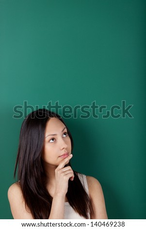 portrait of a pensive young woman against blackboard - stock photo