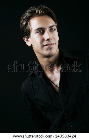 Portrait of a perfectly styled young man on black - stock photo