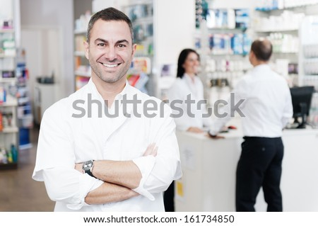 Portrait of a pharmacist.  In the background we can see to a customer served by another pharmacist