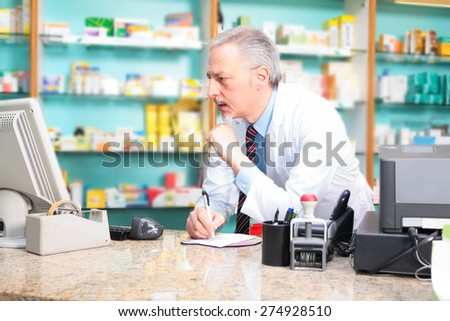 Portrait of a pharmacist using a computer - stock photo
