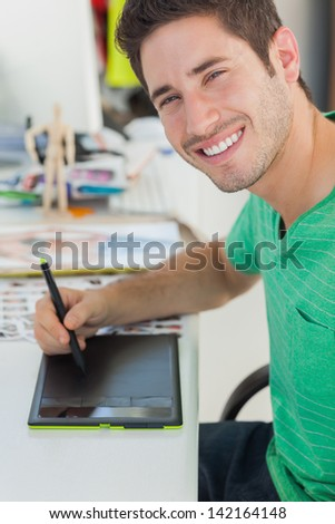 Portrait of a photo editor working on graphics tablet at his desk - stock photo