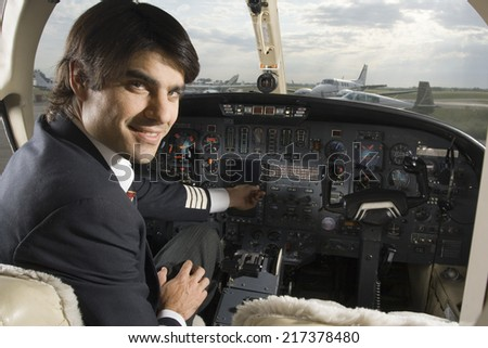 Portrait of a pilot in the cockpit of a private airplane - stock photo