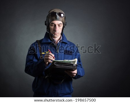 Portrait of a pilot with a geographical map in hand. - stock photo