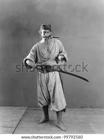 Portrait of a pirate holding a sword and a handgun in his hands with a knife in his mouth - stock photo