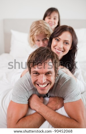 Portrait of a playful family lying on each other in a bedroom - stock photo
