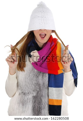 Portrait of a playful young adult woman laughing at the camera with a winter cap covering her eyes. Studio shot on the white background.  - stock photo
