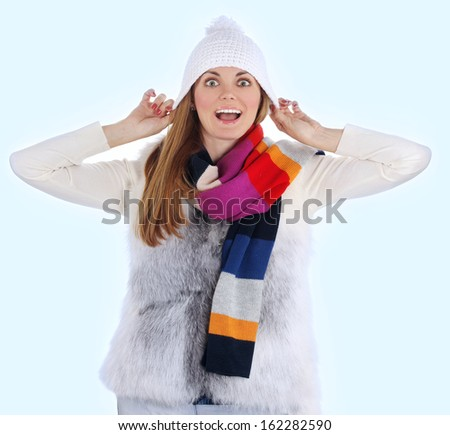Portrait of a playful young adult woman wearing a sweater and a winter hat, laughing at the camera.blue background - stock photo