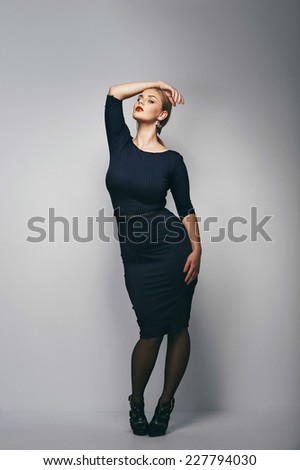 Portrait of a plus size female model posing in black dress over grey background. Beautiful woman with curvy figure. - stock photo