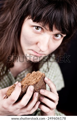 portrait of a poor beggar woman with a piece of bread in her hands - stock photo