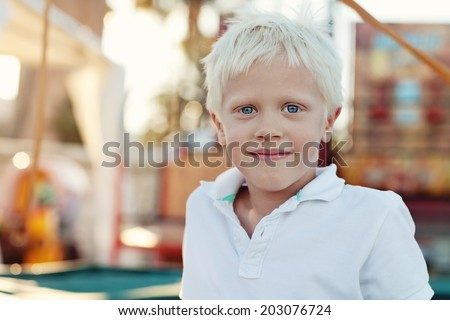 Portrait of a positive blond boy (6 years) with a beautiful blue eyes outdoor.  - stock photo