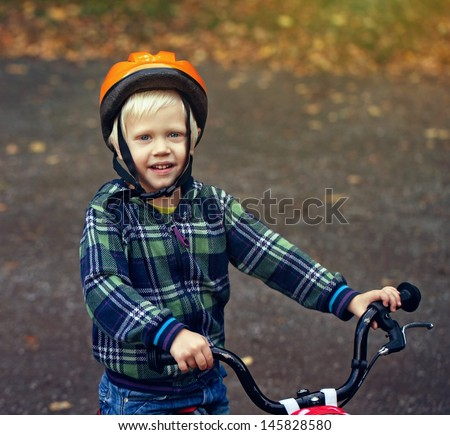 Portrait of a positive little boy on a bicycle outdoor. Age 4 years.  - stock photo