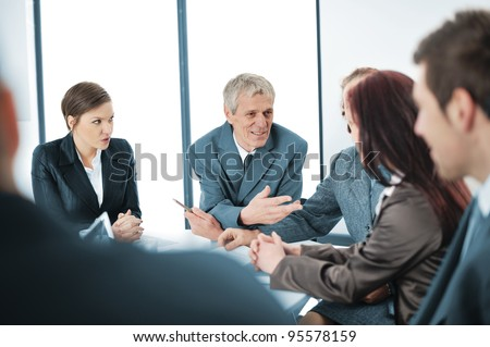 Portrait of a positive manager with his team sitting at the table - stock photo