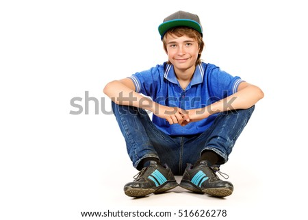 Portrait of a positive teenage boy sitting on a floor and smiling. Studio shot. Teen fashion. Isolated over white.