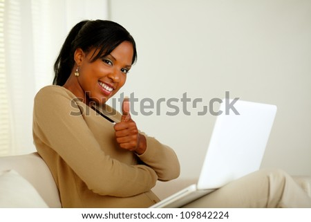 Portrait of a positive young afro-American woman in front her laptop while looking at you and lifting the finger up - stock photo