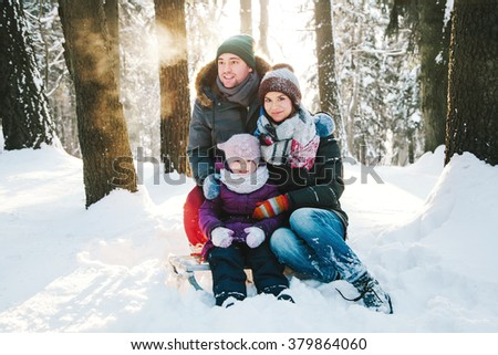 Portrait of a positive young family in the winter forest at sunset and smiling - stock photo