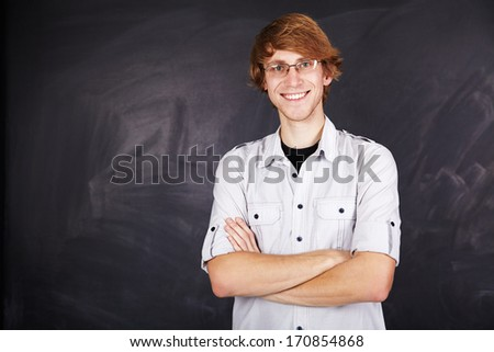 Portrait of a positive young man with glasses on the background of the board