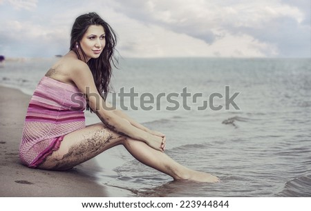 portrait of a pregnant girl sitting on a lake