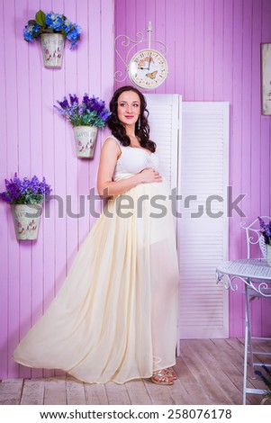 portrait of a pregnant woman in a long light dress - stock photo
