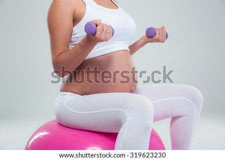 Portrait of a pregnant woman sitting on the fitness ball and workout with dumbbells isolated on a white background - stock photo