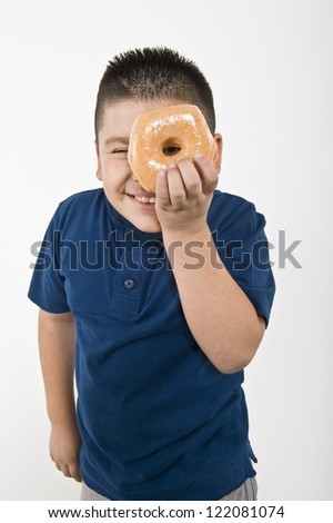 Portrait of a preteen boy looking through donut isolated over white background - stock photo