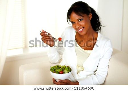 Portrait of a pretty and smiling girl eating a salad and looking at you at home indoor. - stock photo