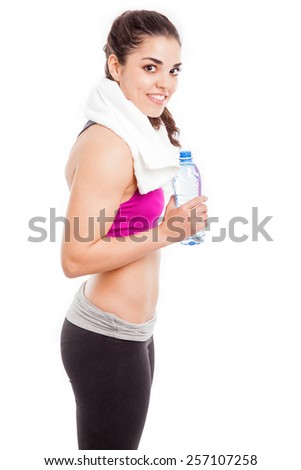 Portrait of a pretty athletic young woman with a towel around her neck drinking some water