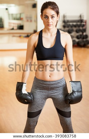 Portrait of a pretty athletic young woman with toned abs wearing boxing gloves in a gym - stock photo