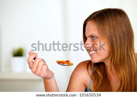 Portrait of a pretty blonde woman eating healthy food at home indoor - stock photo