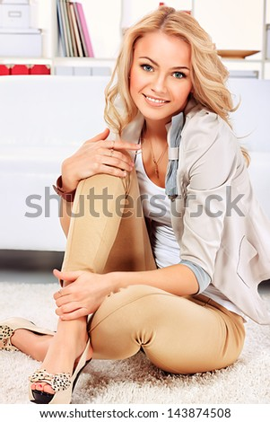 Portrait of a pretty blonde woman sitting on the floor at home. - stock photo