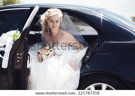 Portrait of a pretty bride in a car.  close-up portrait of a pretty shy bride in a car window. - stock photo