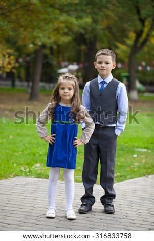 Portrait of a pretty Brother and sister in autumn park - stock photo