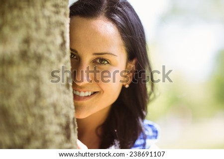 Portrait of a pretty brunette leaning against a tree in the park