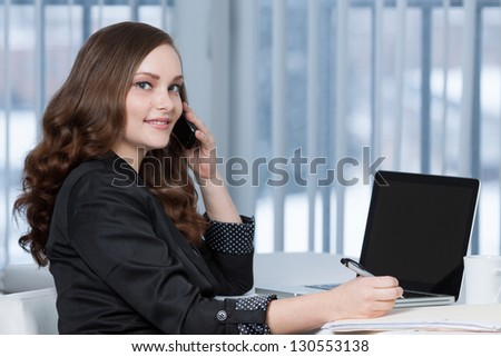 Portrait of a pretty business woman at office desk writing on document while talking on telephone.