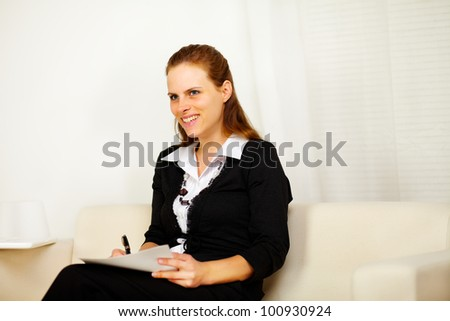 Portrait of a pretty business woman smiling and working with a laptop and documents - stock photo