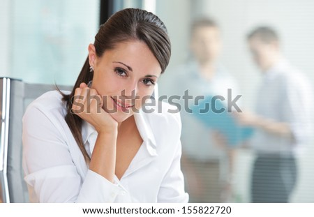 Portrait of a pretty business woman smiling, blurred colleagues in the background  - stock photo