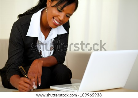 Portrait of a pretty businesswoman on black suit working while sitting on couch in front of her laptop - stock photo