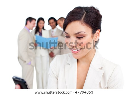 Portrait of a pretty businesswoman sending a text with her team on the background - stock photo