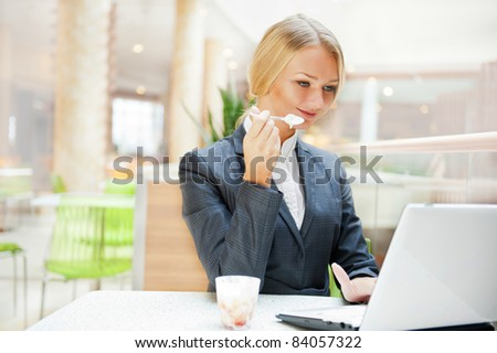 Portrait of a pretty businesswoman sitting at cafe with a laptop using wireless internet, having dessert after lunch - stock photo