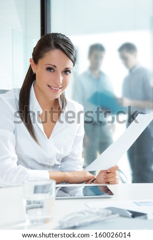 Portrait of a pretty businesswoman smiling, blurred colleagues in the background  - stock photo