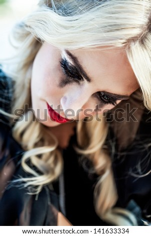portrait of a pretty caucasian girl with curly blond hair bending her head in sadness while her black glitter make-up is smudged down her cheeks - stock photo