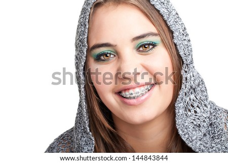 portrait of a pretty caucasian girl with hazel eyes smiling showing her braces wearing a hooded gray jersey - stock photo