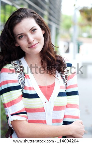 portrait of a pretty college student on campus - stock photo