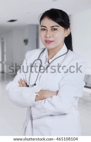 Portrait of a pretty female doctor with her arms crossed and standing in the hospital